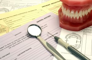 Dental model and tools on top of patient forms.